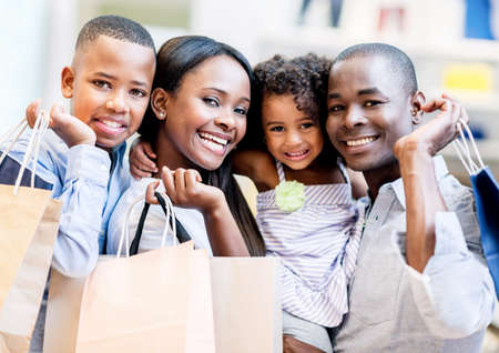 malls: Happy shopping family smiling together at the mall Stock Photo