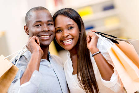 Portrait of a happy shopping couple holding bags Stock Photo - 21615883