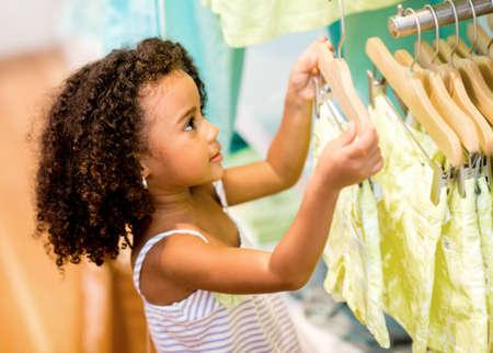 compras compulsivas: Comprador mujer joven en una tienda en busca de ropa Foto de archivo