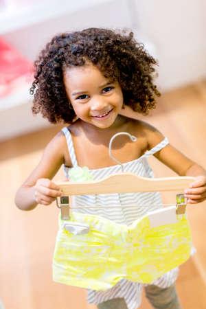compras compulsivas: Ni�a de compras para la ropa linda y sonriente Foto de archivo