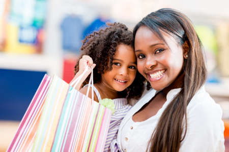 Happy shopping girls holding bags and smiling photo