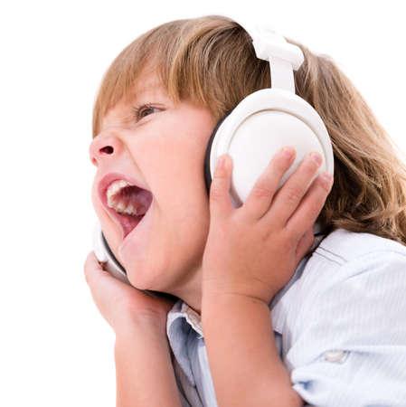 niño cantando: Niño pequeño que escucha música con auriculares - aisladas sobre fondo blanco