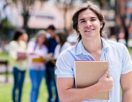 Happy college student holding a notebook outdoors photo
