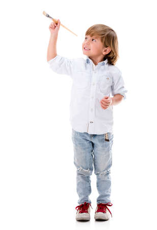 Happy boy painting with a brush - isolated over white background photo