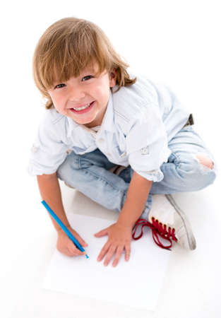 Happy little boy coloring - isolated over a white background photo