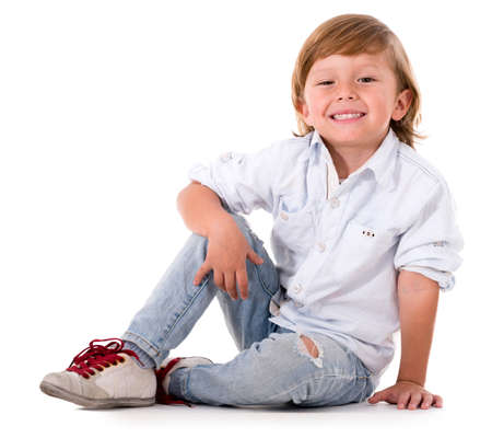 naughty boy: Happy cute boy sitting on the floor - isolated over white background