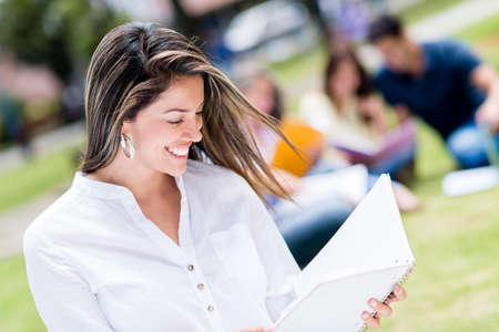Happy female student holding a notebook outdoors photo