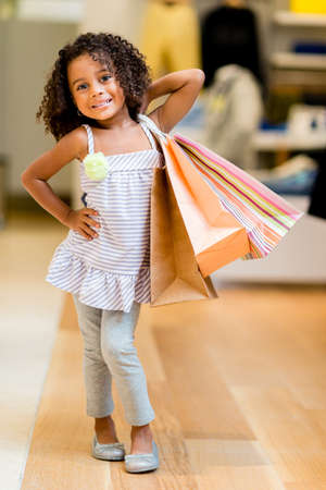 Beautiful shopping girl at a retail store holding bags photo