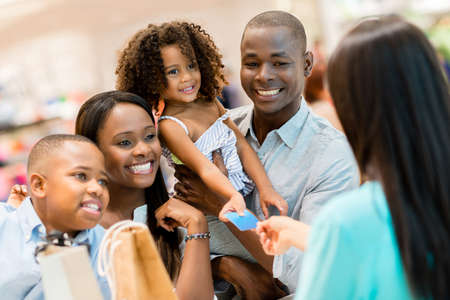 Happy shopping family at the cashier paying for their purchases photo