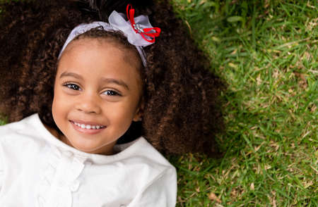 Portrait of a beautiful happy little girl lying outdoors photo