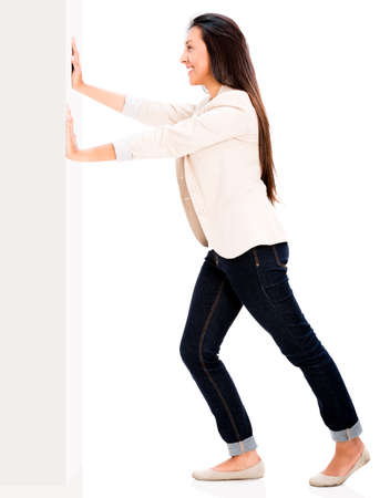 Woman pushing a wall - isolated over a white background photo