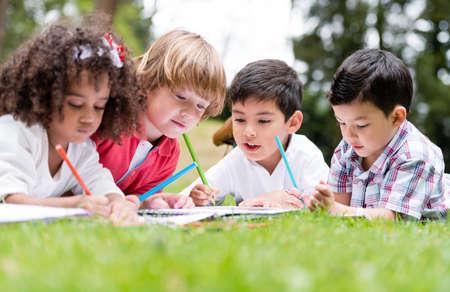ni�os con l�pices: Grupo de escuela de los ni�os para colorear aire libre que parece feliz Foto de archivo