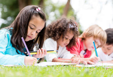 school friends: Happy group of children coloring at the park Stock Photo