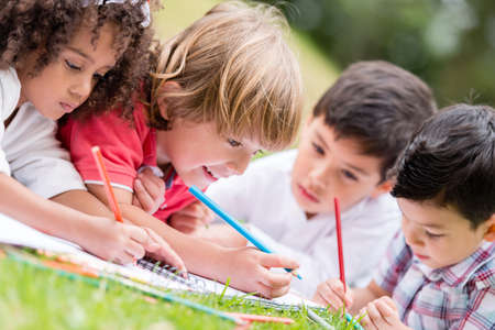 Group of kids coloring outdoors and looking happy Stock Photo