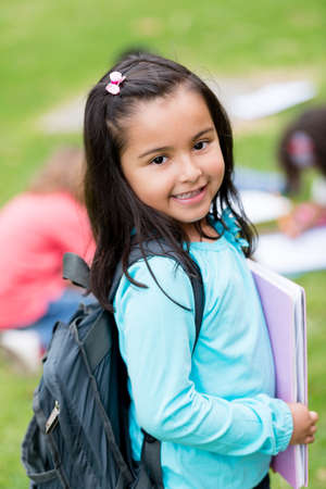 backpack school: Beautiful school girl looking very happy outdoors Stock Photo