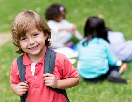 kinder: Ni�o de la escuela feliz celebraci�n de su bolsa y sonriente