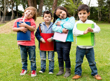 children playing together: Happy group of school kids holding notebooks outdoors Stock Photo