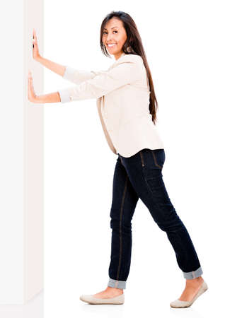 Happy woman pushing the wall - isolated over white background photo