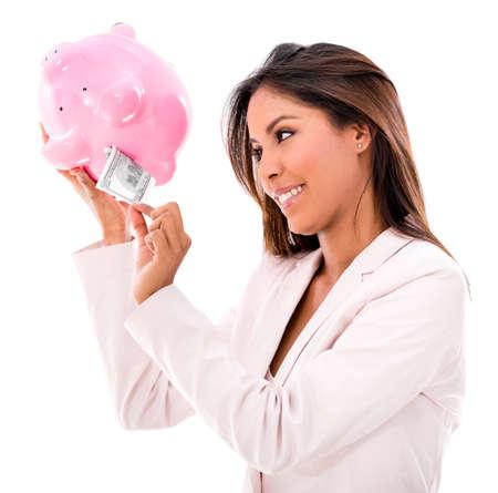 coinbank: Mujer de negocios que toma dinero de una hucha - aislado m�s de blanco Foto de archivo