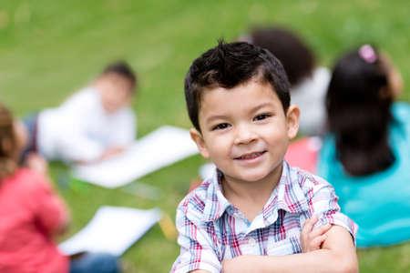 Netter Junge in der Schule suchen sehr glücklich im Freien Lizenzfreie Bilder