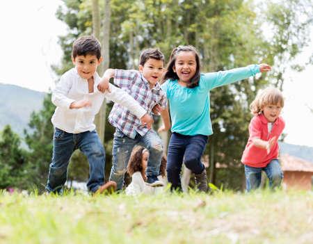 ni�os jugando en el parque: Feliz grupo de ni�os jugando en el parque