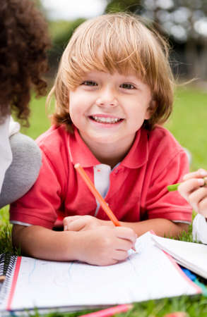 Happy school boy coloring a book and smiling outdoors photo
