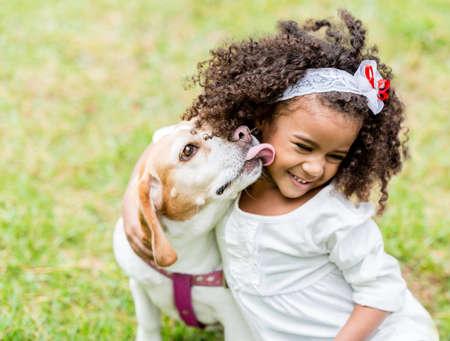 mujer perro: Ni�a feliz con un perro que lame la cara Foto de archivo