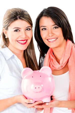 coinbank: Mujeres felices mantenimiento de ahorros en una hucha - aislados en un fondo blanco Foto de archivo