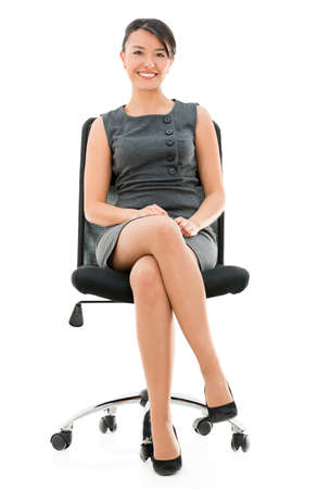 businesswoman legs: Happy business woman sitting on a chair - isolated over white background