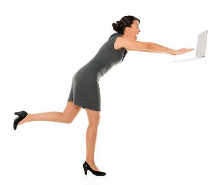 hustle: Donna d'affari in una corsa di lavoro su un computer portatile - isolato su sfondo bianco Archivio Fotografico