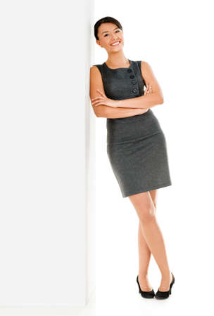 Business woman leaning against the wall - isolated over white background photo