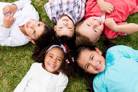 girotondo bambini: Buon gruppo di ragazzi sdraiato sul pavimento in un cerchio