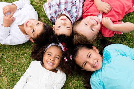 friendship circle: Happy group of kids lying on the floor in a circle Stock Photo