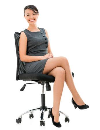 mujer sentada: Mujer de negocios feliz sentado en una silla - aislada sobre fondo blanco Foto de archivo