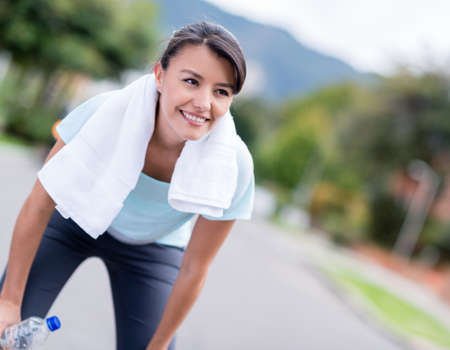 Fit woman resting while running in the city and smiling photo