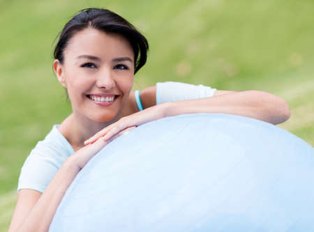 Happy woman doing Pilates outdoors with a fitness ball photo