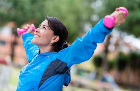 woman arms up: Happy woman exercising with arms up and free-weights