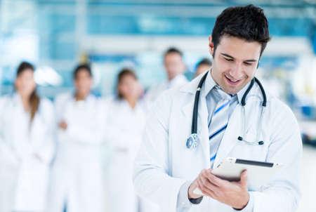 medico computer: Medico felice utilizzando il computer tablet in ospedale