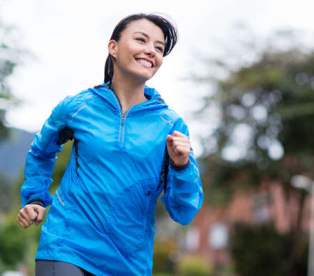 jogging track: Fit woman running outdoors looking very happy Stock Photo