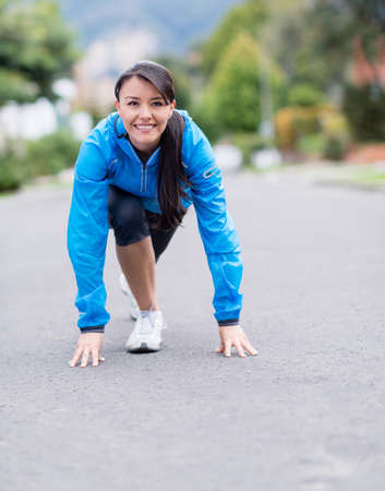 Fit woman in a position ready to run outdoors photo