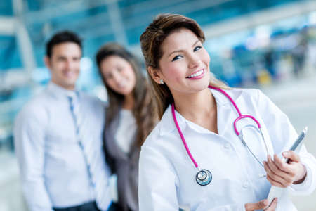Family doctor at the hospital with patients at the background photo