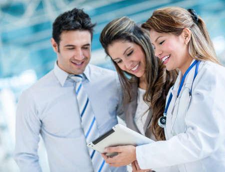 Hausarzt mit einem glücklichen Paar im Krankenhaus