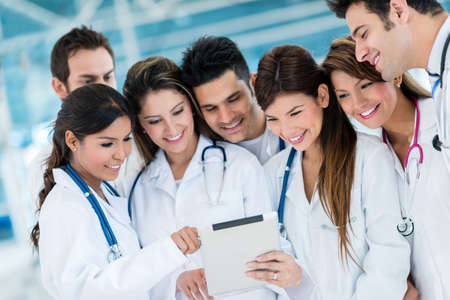 Group of doctors using health app on a tablet computer photo