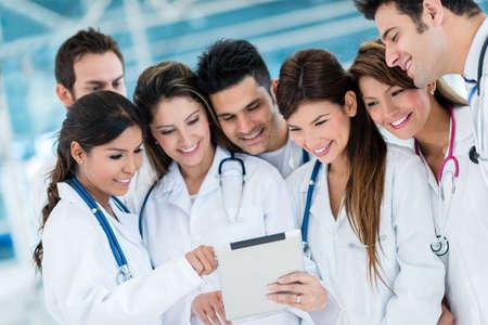 Gruppe von Ärzten mit Gesundheits-App auf einem Tablet-Computer Lizenzfreie Bilder