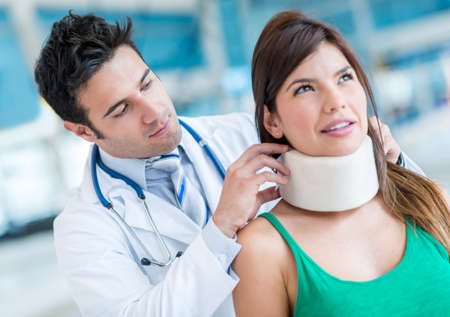 Woman in pain at the doctor for a neck injury photo