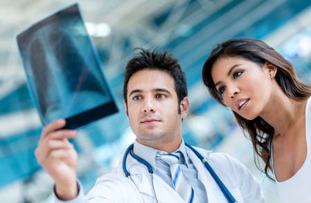 calamity: Male doctor looking an x-ray  with a patient Stock Photo