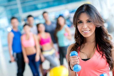 lifting weights: Mujer en el gimnasio levantando pesas y mirando feliz