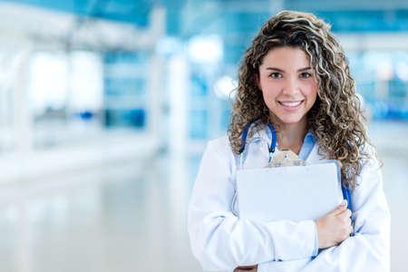 Glücklich weiblichen Doctor holding Zwischenablage im Krankenhaus