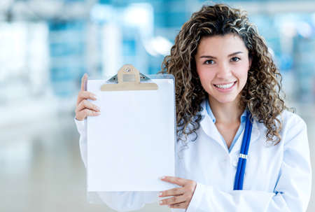 Female doctor holding a clipboard with a white paper photo