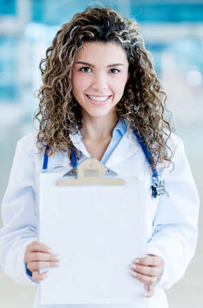 Doctor showing a blank paper on a clipboard - to edit photo
